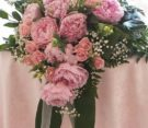 centrotavola cadente con peonie, rose e lisianthus rosa, nebbiolina e foglie di aspidistria