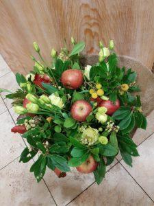 bouquet autunnale con bacche e foglie di corbezzolo, mele fresche e lisianthus