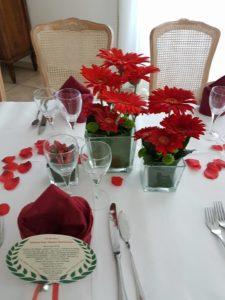 centrotavola con gerbere rosse e santini in cubo di vetro