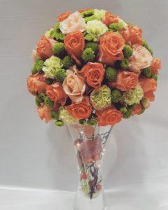 composizione autunnale in spugna con rose arancioni e salmone, santini e garofani su base di vetro con foglie di quercia, melette e micro luci led
