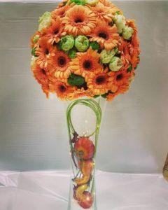 composizione autunnale in spugna con gerbere arancioni, santini e rose ranuncolo bianche screziate di verde su base di vetro con foglie di quercia, zucche finte e micro luci led